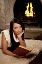 Girl lying near the fireplace and reads a book Royalty Free Stock Photography