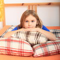 Girl lying on pillows smiling tired kid with opened eyes in a bed Stock Photography