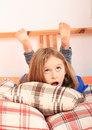 Girl lying on pillows surprised kid rolling eyes in a bed Royalty Free Stock Photo