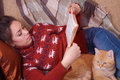Girl lying on the sofa with red cat and reading a Royalty Free Stock Photo
