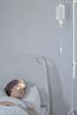 Girl lying under drip young with cancer in hospital Royalty Free Stock Photo