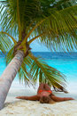 Girl is lying under palm tree. Luxury Holidays. Royalty Free Stock Photography