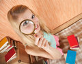 Girl with magnifier against books Royalty Free Stock Images
