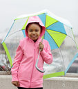 Girl maintains cheerful attitude despite gloomy rainy wet weather outside Royalty Free Stock Photos
