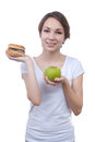 Girl makes choice between apple and hamburger isolated on white Royalty Free Stock Images