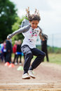 Girl makes long jump Royalty Free Stock Photo