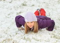 Girl making angel in snow little kid smiling lila winter jacket and red pants with gloves and cap playing and sliding Royalty Free Stock Photography