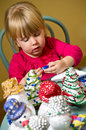 Girl making christmas decorations a cute little sitting at a table and Stock Photo
