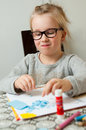 Girl making paper artwork pretty blonde wearing spectacles seated at a table with and a tube of glue Royalty Free Stock Image