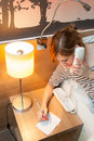 Girl making a phone call young pretty using and writing note in her bedroom or in hotel room Royalty Free Stock Photos