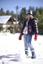Girl making snowballs portrait of pretty smiling young dressed in warm winter clothes including hat gloves and boots outside Stock Images
