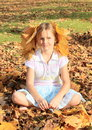 Girl with maple leaves small kid smiling blond long hair decorated sitting in fallen on autumn Stock Photography