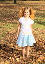 Girl with maple leaves small kid smiling blond long hair decorated standing in fallen on autumn Stock Image