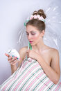 Girl marshmallow with a pillow and alarm clock in her hands afra afraid of being late makeup the style of Royalty Free Stock Images