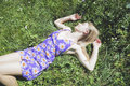 Girl on a meadow blonde laying down lawn grass Royalty Free Stock Image