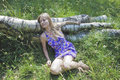 Girl on a meadow blonde laying down tree trunk in the grass Stock Images