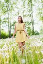 Girl in a meadow young among dandelions summer day Royalty Free Stock Image