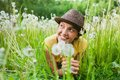 Girl in a meadow young among dandelions summer day Royalty Free Stock Images