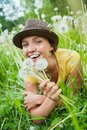 Girl in a meadow young among dandelions summer day Royalty Free Stock Photo