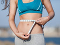 Girl measuring her waist sexy abdomen and hands of young woman with tape on open air horizontal composition Stock Images