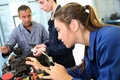 Girl in mechanics class training with teacher and students Stock Image