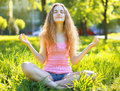 Girl meditates outdoors on the grass Stock Images