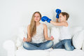 Girl meditating boy in boxing gloves wants to hit him sitting on the couch and wake up Stock Image