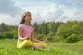 Girl meditating on the green meadow Stock Photos