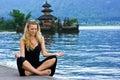 Girl meditating at the lake on Bali Royalty Free Stock Photo