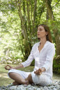 Girl meditating in lotus position by forest river full length of teenage Stock Photography