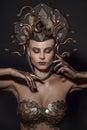 Girl Medusa headdress of gold color on a black background Royalty Free Stock Photo