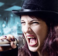 Girl with microphone in  black top-hat Royalty Free Stock Image