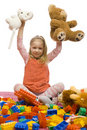 Girl in the middle of toy-mess Stock Photography