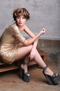 Girl model wearing luxurious gold dress and platform sandals Royalty Free Stock Photo