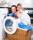 Girl and mom near washing machine Royalty Free Stock Photo