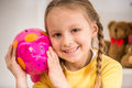 Girl with moneybox little pretty smiling in yellow pullover holding piggy Stock Image