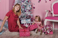Girl and mother near christmas fir tree with gifts Royalty Free Stock Photography