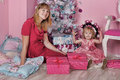 Girl and mother near christmas fir tree with gifts Stock Image