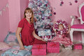 Girl and mother near christmas fir tree with gifts Stock Images