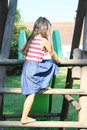 Girl mounting on stairs to slide barefoot little in blue red and white dress wooden green Stock Photography