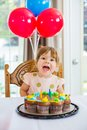 Girl with mouth open sitting in front of cake happy at home Stock Photography