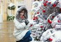 Girl near christmas tree covered with snow a Royalty Free Stock Image