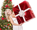 Girl near christmas tree holding red gift box. Stock Images