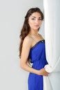 Girl near curtains posing in studio blue dress Royalty Free Stock Photography