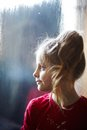 Girl near the frozen window in expectation spring Royalty Free Stock Images