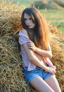 The girl near a haystack in the unbuttoned shirt Royalty Free Stock Photo