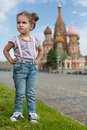 Girl near the saint basils cathedral little in jeans with suspenders with hands on hips Royalty Free Stock Photography