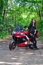 The girl near a sports bike in the woods sits motorcycle Stock Photography