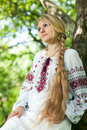 Girl near the tree beautiful young in peasant dress stands a woman with a long braid in russian national clothes not looking at Stock Photos