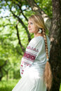 Girl near the tree beautiful young in peasant dress stands a woman with a long braid in russian national clothes not looking at Royalty Free Stock Images